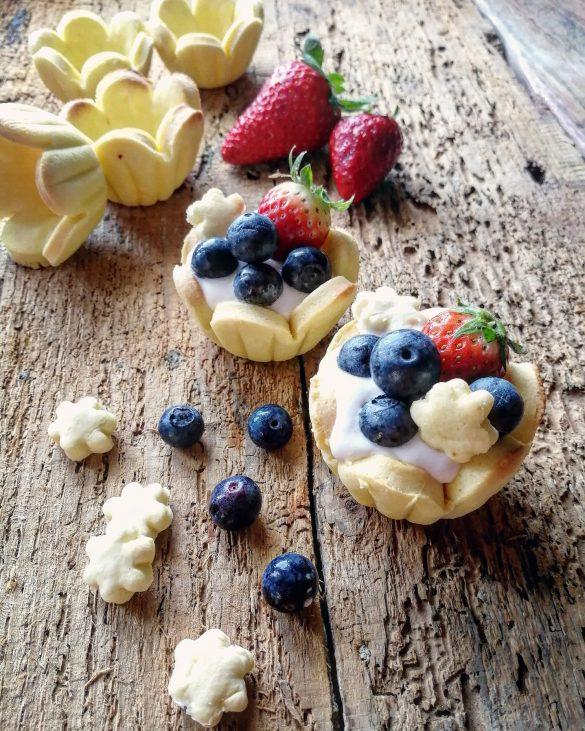 crostatine di frolla con crema e frutta, posate su un tavolo di legno,con fragole e mirtilli