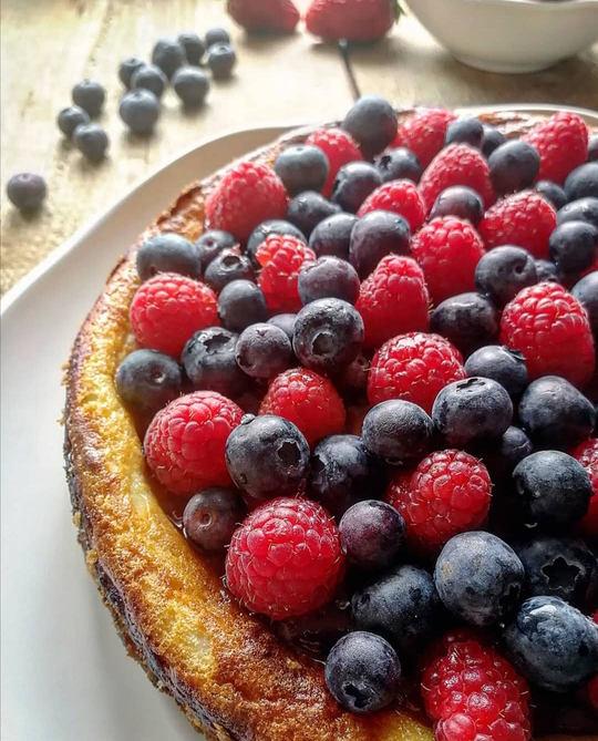 cheesecake a metà in primo piano con mirtilli e lampono, su un piatto bianco
