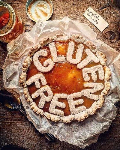 crostata rotonda con scritta gluten free di frolla, su un tavolo di legno,con un barattolo di marmellata aperto