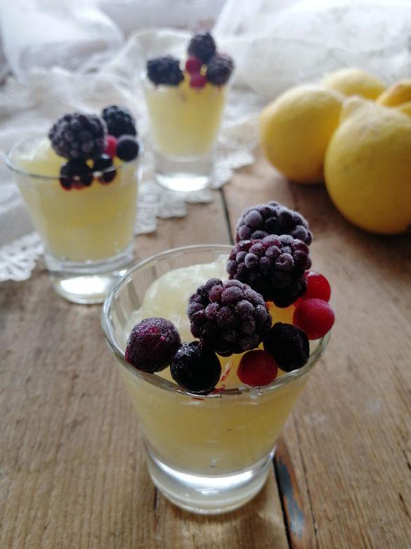 bicchierini con crema al limone e frutti di bosco, posati su un tavolo di legno con dei limoni sullo sfondo