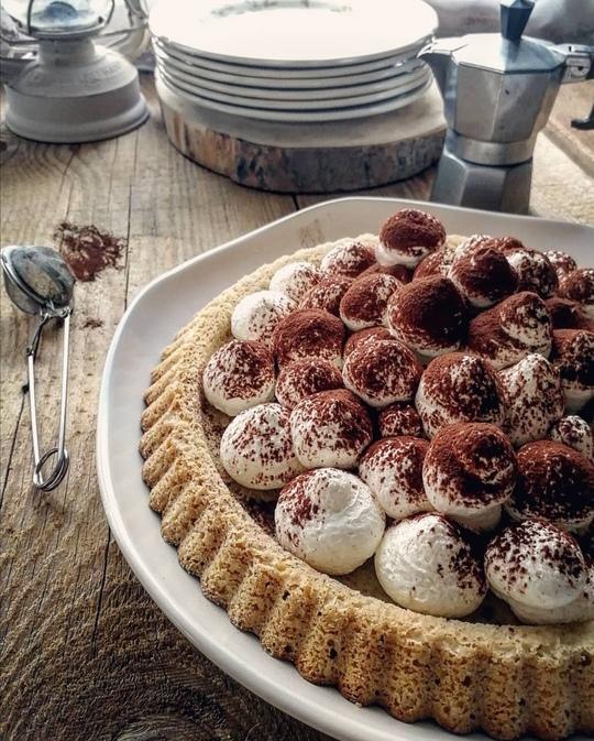 crostata morbida con palline di crema sopra,spolverate di cacao. Posata su un tavolo di legno,con dei piattini e una moka sullo sfondo