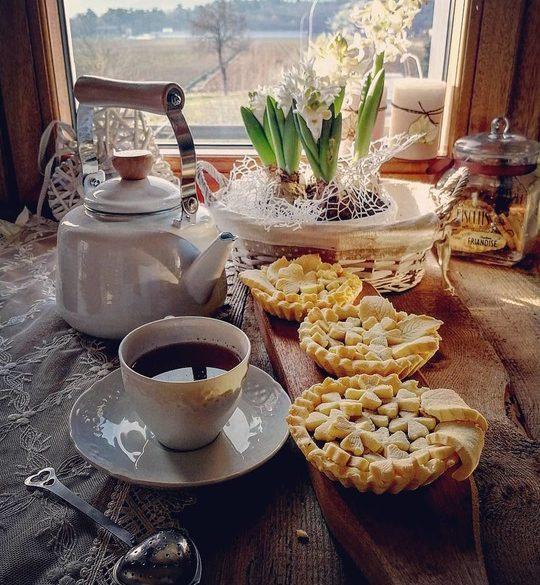 una finestra con sotto una teiera,dei fiori,una tazza di the, delle crostatine decorate