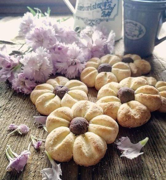 biscotti a forma di fiore posati su un tavolo di legno, sullo sfondo dei fiori rosa,una brocca e una tazzina