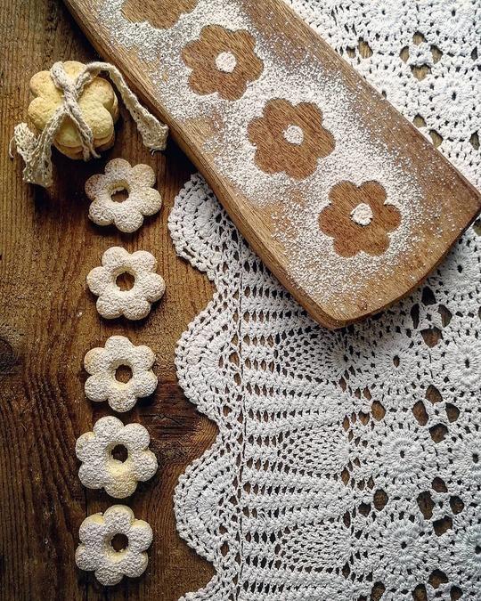 biscotti a forma di fiorellini su un tavolo di legno, visti dall'alto, con un tagliere e un centrino in pizzo