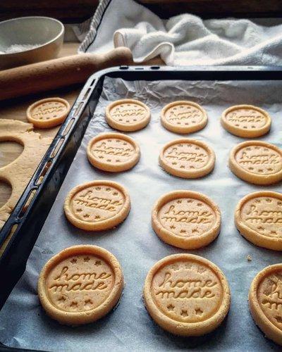biscotti rotondi con scritta home made su una teglia da forno posata su un tavolo con un mattarello