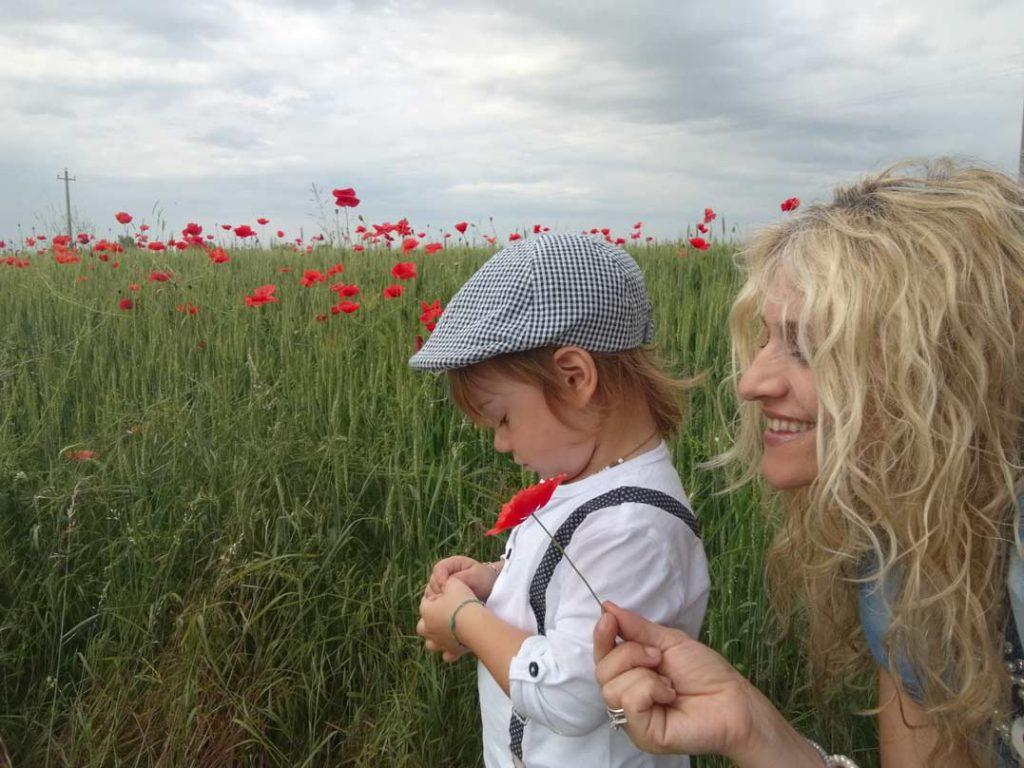 una mamma e suo figlio in un campo di papaveri