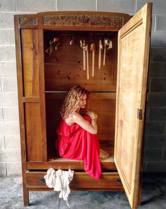 donna vestita di rosso seduta dentro un armadio con l'anta aperta