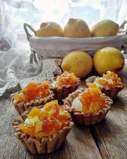 cestini di frolla con crema al limone e pezzetti di buccia di limone come decorazione, un cesto di limoni sullo sfondo