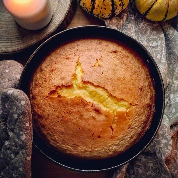 torta rotonda ripreso dall'alto sopra una tavola con una candela e delle zucche