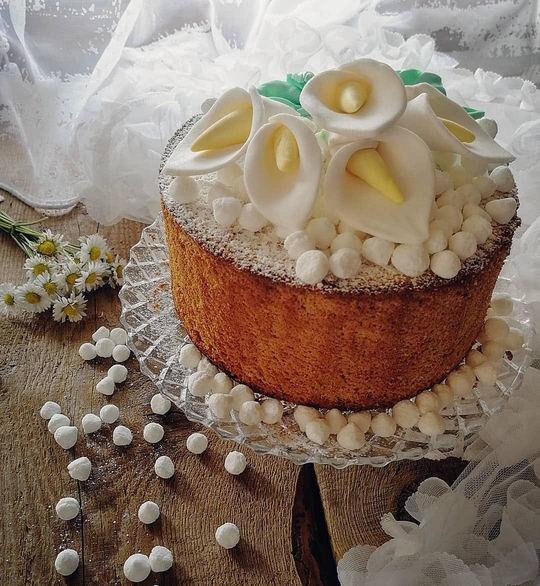 un dolce rotondo su un'alzata di cristallo, decorato con calle in pasta di zucchero e tante piccole meringhe rotonde.Sullo sfondo delle margherite .