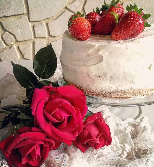 torta di panna alta sopra un alzata di vetro, vista di lato , con fragole sopra e delle rose posate sul tavolo con un pizzo