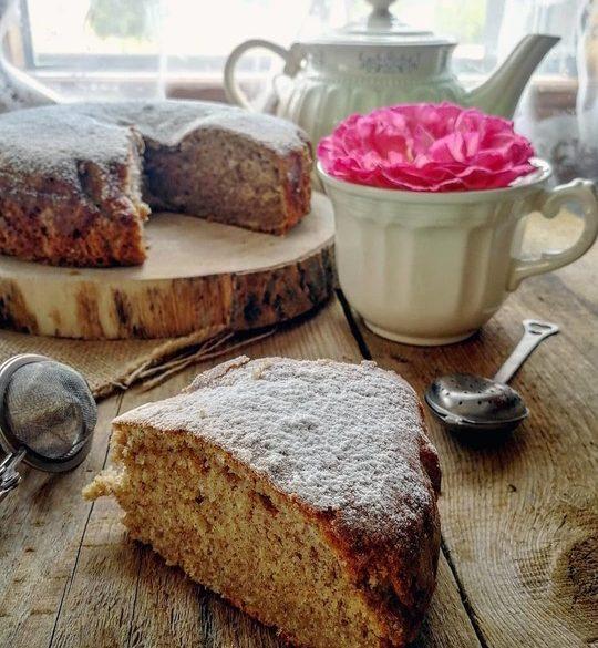 torta posata su un tavolo di legno, una fetta tagliata in primo piano, una tazza con una rosa dentro e una teiera sullo sfondo