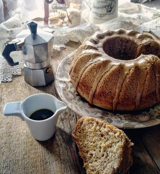 una ciambella glassata,posata su un tavolo, con una tazzina di caffè e una moka e una fetta tagliata posata