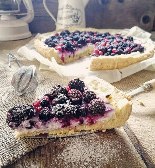 una fetta di crostata con ricotta e frutti rossi in primo piano, sullo sfondo sul tavolo la torta tagliata.