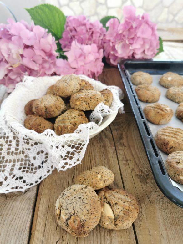 dei biscotti in primo piano, una ciotolina bianca piena di biscotti sullo sfondo con dei fiori rosa e a lato una teglia con altri biscotti