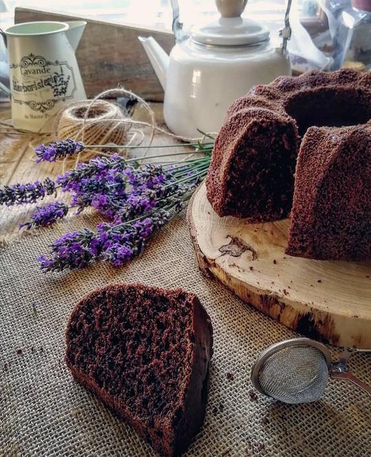 ciambella al cacao tagliata ,una fetta caduta sul tavolo,un mazzo di lavanda e sullo sfondo una teiera