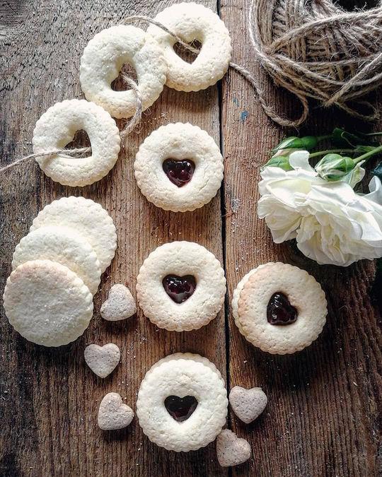 biscottini con ripieno di marmellata visti dall'alto posati su un piano di legno insieme ad una rosa bianca