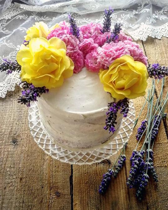 torta bianca con rose gialle,rosa e lavanda come decorazione sopra posata su un tavolo con dei rametti di lavanda