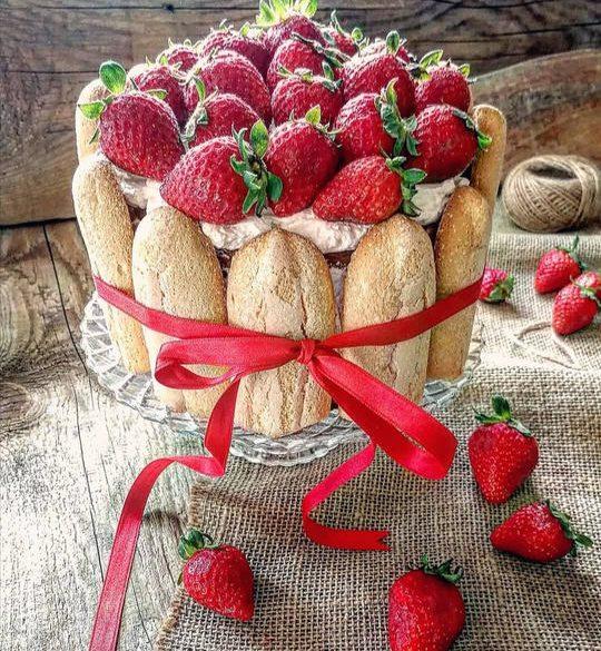 torta con fragole a vista, su un piatto da portata, decorata con un nastro. qualche fragole intera sul tavolo