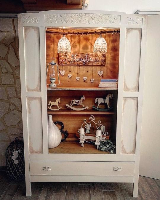 una vetrina aperta ,armadio bianco con interno legno con due mensole, dei cavallini a dondolo ,due lampadari e una targa di legno con scritto famiglia