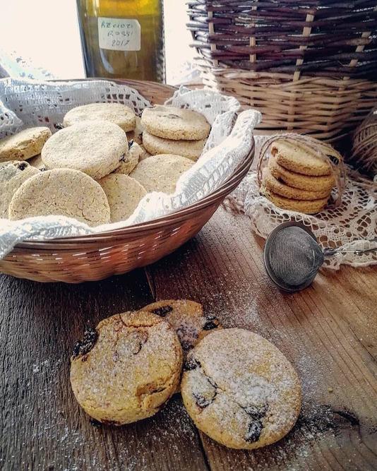 un cestino di biscotti con 3 biscotti posati sul tavolo coperti da zucchero a velo. sullo sfondo una bottiglia di vino