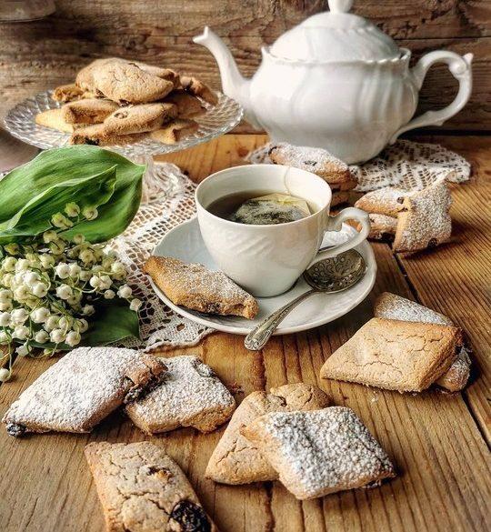 un tavolo di legno dove sono disposti biscotti a forma di rombo, una tazza bianca con del thè e una teiera bianca sullo sfondo con un mazzetto di fiori mughetto e altri biscotti su una alzata di vetro.