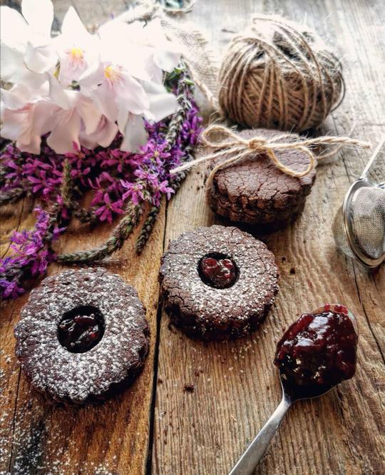 biscotti al cacao farciti di marmellata spolverati da zucchero a velo psati su un tavolo, visti dall'alto, con un cucchiaino colmo di marmellata. Vicino dei fiori e un gomitolo, altri biscotti uniti da un cordoncino