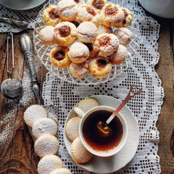 biscotti visti dall'alto con una tazza di the e una tovaglietta in pizzo