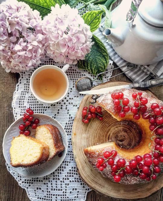 ciambella vista dall'alto con ribes, un piattino con due fette, una tazza di the, una teiera e delle ortensie rosa