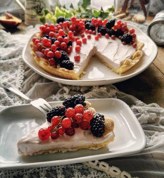 una fetta di torta con frutta in primo piano, sullo sfondo la torta tagliata e tanti frutti sopra.