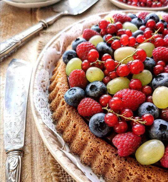 una crostata morbida vista dall'alto con tantissima frutta colorata, un coltello antico a lato