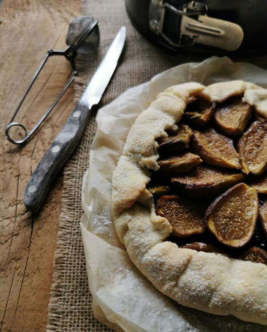 una crostata con dei fichi posata su carta forno, sipra un tavolo di legno, vista per metà e dall'alto con un coltello di fianco