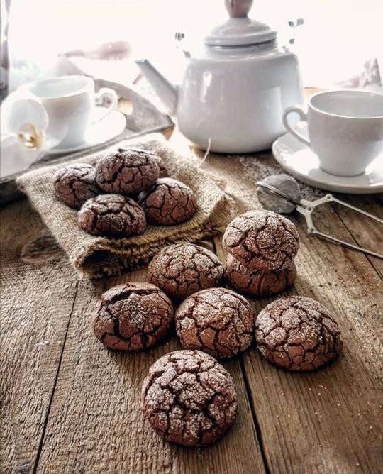biscotti al cioccolato su un tavolo di legno e sullo sfondo una teiera e delle tazze