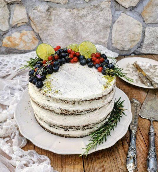 una torta al cioccolato alta con panna, mirtilli,ribes,fette di lime e del rosmarino a bordo del piatto. Sopra un piano di legno con un pizzo a lato e delle pietre sullo sfondo