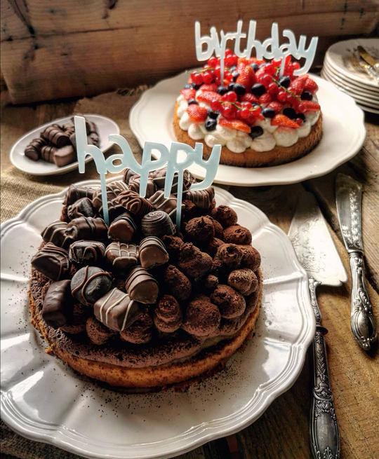 due torte di compleanno, una al cioccolato in primo piano,l'altra con frutti rossi sullo sfondo,sopra piatti bianchi su un tavolo di legno