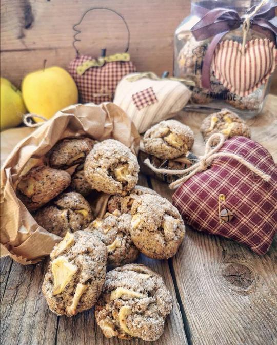 biscotti rustici che escono da un sacchetto di carta posato su un tavolo con delle mele di stoffa e sullo sfondo 2 mele gialle