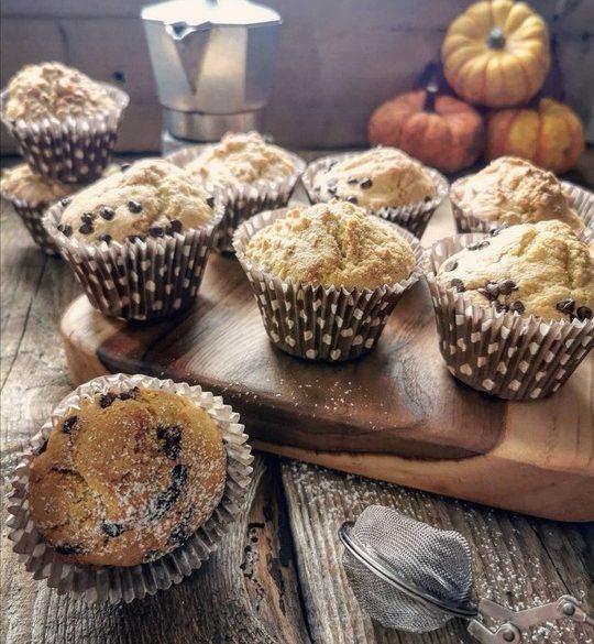muffins su un tagliere e uno in primo piano rovesciato, sullo sfondo una moka e delle zucche