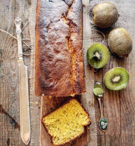 un plumcake visto dall'alto con fetta tagliata e dei kiwi a lato con un coltello
