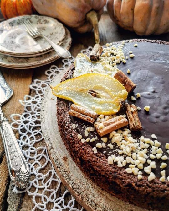 una torta al cioccolato fondente su un tavolo di legno, con sullo sfondo dei piattini vintage e delle zucche