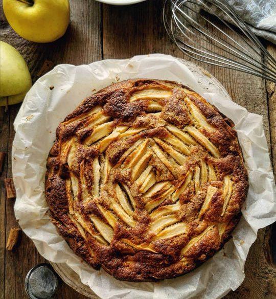 una torta di mele vista dall'alto posata su un tavolo con carta forno e delle mele gialle a lato