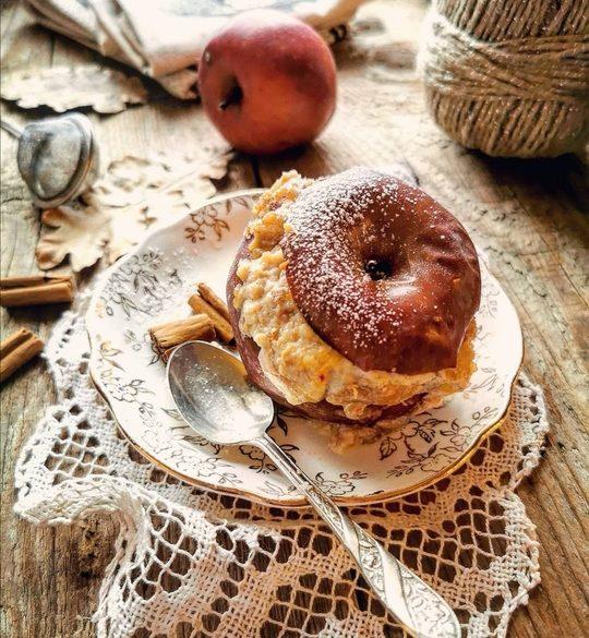 una mela rossa cotta sul piattino, con farcia di ricotta, a lato un cucchiaino e sullo sfondo una mela rossa e un gomitolo