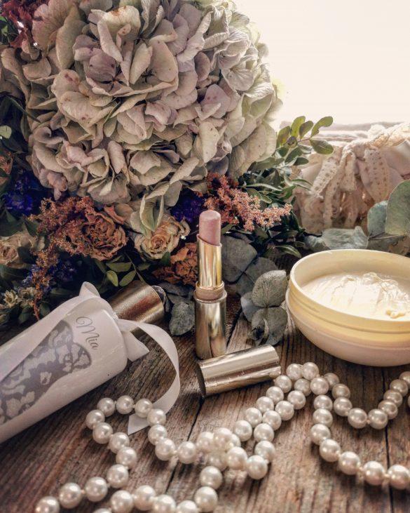 un rossetto, una crema, un profumo, un bouquet e una collana di perle sopra un tavolo di legno