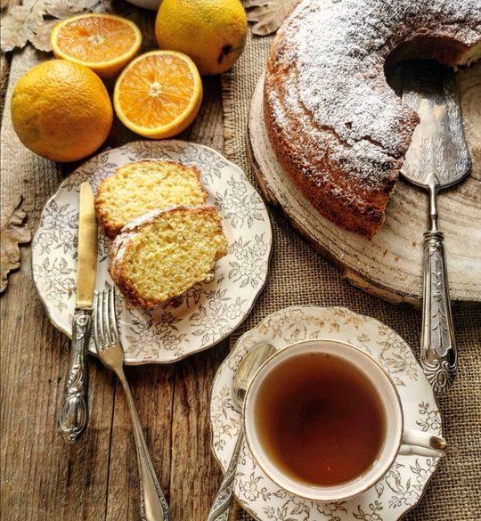 una tazza di tè vista dall'alto, un piattino con 2 fette di torta e una ciambella tagliata con delle arance