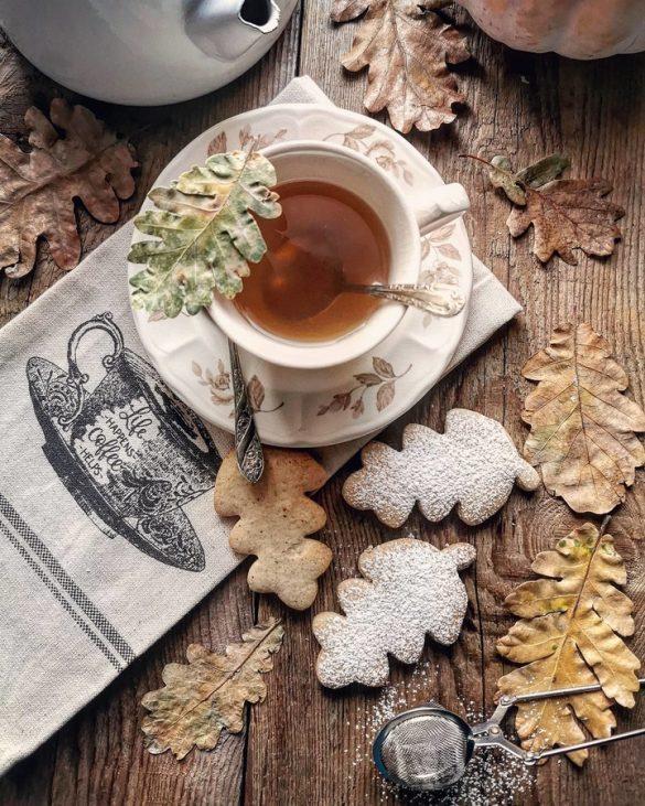 una tazza vista dall'alto con del the, dei biscotti a forma di foglie con delle foglie secche, su un tavolo di legno e una tovaglietta bianca con disegnata una tazza