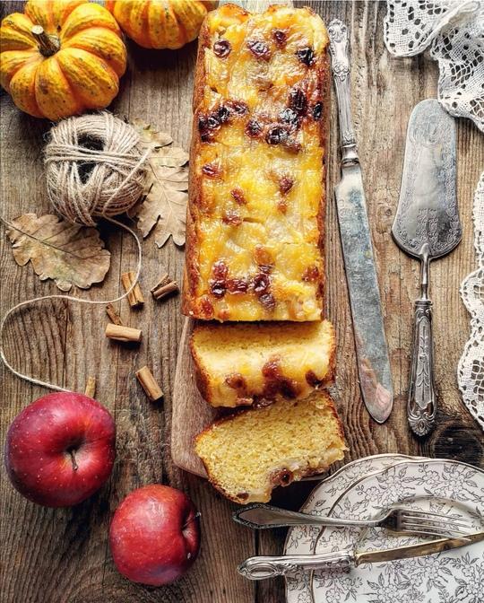 un plumcake tagliato visto dall'alto, posato su un tagliere, con a lato delle mele rosse, un gomitolo,dei piattini e posate vintage