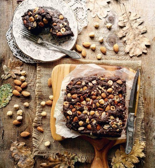 torta al cioccolato quadrata vista dall'alto, ricca di frutta secca, di lato un piattino con due pezzetti di torta e intorno foglie secche e frutta secca.