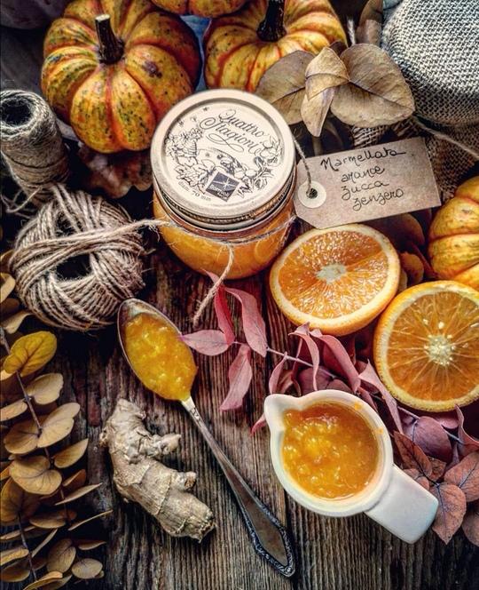un tavolo con vazetto di marmellata, delle arance tagliate viste dall'alto, un cucchiaio con della marmellata arancione, dello zenzero e un gomitolo di filo