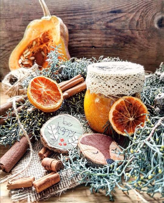 un vasetto di marmellata arancione, con una fettina di arancia come decorazione, in primo piano con cannella,rametti verdi, una zucca tagliata