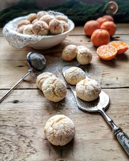 biscotti su un tavolo di legno, con una ciotola sullo sfondo e dei mandarini