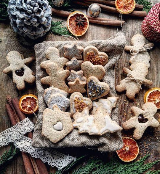 biscotti di Natale visti dall'alto, decorati con brillantini e glassa, un ramo verde e delle arance essiccate